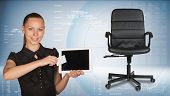 Businesswoman holding tablet PC and business card. Office chair beside