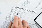 Hand With Pen And Eyeglasses Over Agreement