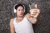 Attractive Man With Headphones Unhappy To Make Selfie With His Mobile Phone