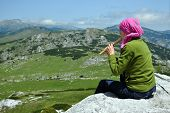 Girl Playing On Flute In The Mountains