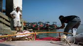 PULAU KETAM, MALAYSIA - JANUARY 18, 2015: A boatman prepares to dock a ferry at a fisherman's wharf in Pulau Ketam (Crab Island), famous for trading in fish, sea food products and catch from the sea.