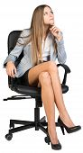 Businesswoman on office chair with her finger under chin, looking upwards