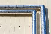 Metal Chrome Pipes On Siding Wall