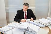 Businessman With Heap Of Folders On Desk
