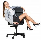 Businesswoman on office chair with her legs over armrest