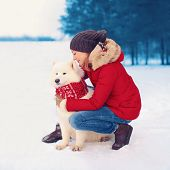 Christmas, Winter And People Concept - Happy Woman Owner Embracing White Samoyed Dog Outdoors