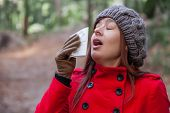 image of overcoats  - Young woman with a cold or flu sneezing on a white paper handkerchief on a forest wearing a red overcoat - JPG