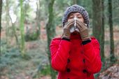 stock photo of overcoats  - Young woman suffering from a cold or flu blowing her nose on a white paper handkerchief on a forest wearing a red overcoat - JPG