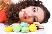 Young cute girl with tasty macaroon on white background