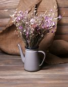 Bouquet of dried flowers on table and wooden planks background
