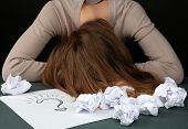 Tired woman at desk with question mark sheet of paper, on dark background