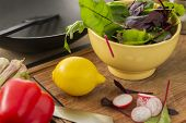 stock photo of rocket salad  - Fresh ingredients for making a salad on a chopping board in the kitchen with sliced radish rocket baby spinach and herbs in a bowl red bell pepper and a ripe yellow lemon - JPG