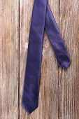 Trendy tie on wooden planks background