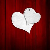 Concept or conceptual two white old paper vintage hearts nailed on red wood or wooden background for Valentine`s day