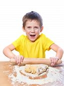 Happy Boy Kneads And Rolling Dough For Pie On Kitchen Table