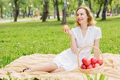 Young pretty woman in summer park with apple