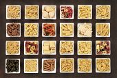 Large italian pasta dried food collection in square bowls over brown lokta paper background.