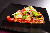 foto of hot fresh pizza  - Colorful pizza piece with tomatoes ham fresh herbs on black plate on dark background - JPG