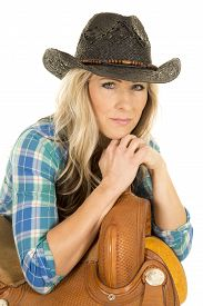 stock photo of western saddle  - a cowgirl in her blue plaid shirt wearing her black western hat leaning on a saddle - JPG