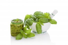 foto of basil leaves  - Basil pesto in glass jar and fresh basil leaves in mortar isolated on white background - JPG