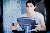 picture of cardio  - Woman riding an exercise bike in gym - JPG