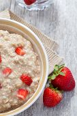 picture of porridge  - close up view of oatmeal porridge with strawberry on color back - JPG