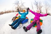 stock photo of snow-slide  - Children with arms up sliding down on the tubes together during beautiful winter day with trees trunks on the background - JPG