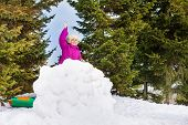 picture of snowball-fight  - Small girl with snowball in her hand stands behind the snow wall with forest on the background - JPG