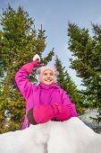stock photo of snowball-fight  - Happy girl ready to throw snowball while standing behind the snow wall with fir forest on the background during beautiful winter day - JPG