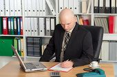 pic of bald head  - young businessman with bald head in the office is writing - JPG
