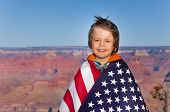 stock photo of bundle  - Portrait of smiling small boy who is bundled up into American flag with Grand Canyon National Park view - JPG