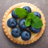 stock photo of curd  - Shortbread home made tartlet filled with lime curd and blueberries on old vintage metal background - JPG