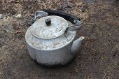 stock photo of kettles  - Old aluminum kettle on a dirty background - JPG