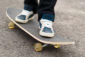 foto of skateboarding  - Skateboarder rides on a skateboard feet in sneakers - JPG