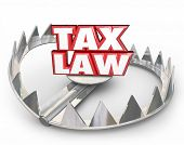 stock photo of trap  - Tax Law words in red 3d letters on a bear trap illustrating legal trouble if you don - JPG