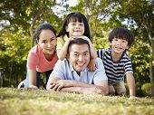 pic of japan girl  - happy asian family with two children taking a family photo outdoors in a park - JPG