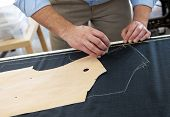 foto of tailoring  - Tailor or clothing designer at work in his studio marking out a pattern for a garment on a length of fabric with chalk close up of his hands - JPG