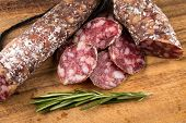 pic of salami  - slices of salami on a wood board as a background - JPG