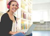 stock photo of legs crossed  - Happy young woman listening to music on stereo headphones as she studies sitting cross - JPG