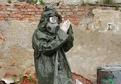 image of gas mask  - Man with gas mask and green military clothes explores small plant after chemical disaster - JPG