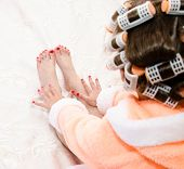 image of hair curlers  - Little girl with manicure and pedicure with hair curlers in bathrobe on bed closeup - JPG