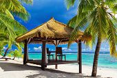 stock photo of gazebo  - Tropical gazebo and two chairs on an sandy island beach with coconut palm trees - JPG