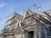 foto of scaffold  - Scaffolds surrounding home following application of smooth exterior stucco but prior to painting - JPG