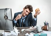 picture of loafers  - Young business man talking on the phone while holding burger in one hand and pencil in the other looking down smiling  - JPG