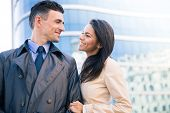 stock photo of flirt  - Happy woman and man flirting outdoors with glass building on background - JPG