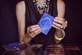 foto of fortune-teller  - Fortune teller forecasting the future with tarot cards on black background - JPG