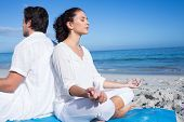 stock photo of beside  - Happy couple doing yoga beside the water at the beach - JPG