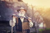 foto of scythe  - Old farmer with scythe taking a break from mowing the grass - JPG