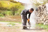stock photo of bricklayer  - Bricklayer cutting a brick with circular saw - JPG