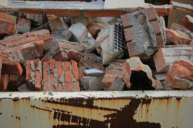stock photo of dumpster  - Bricks in a dumpster near a construction site home renovation - JPG